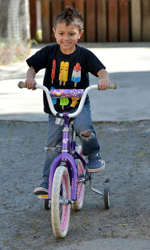 Julian Meija-Blagovic, 4, of Martinez, rides a pink and white bike that his parents bought for him at a garage sale in Martinez, Calif., on Saturday March 23, 2013.  His parents, Jorge Meija and Lisa Blagovic,  are trying to raise their kids with respect and balance of gender. (Dan Rosenstrauch/Staff)