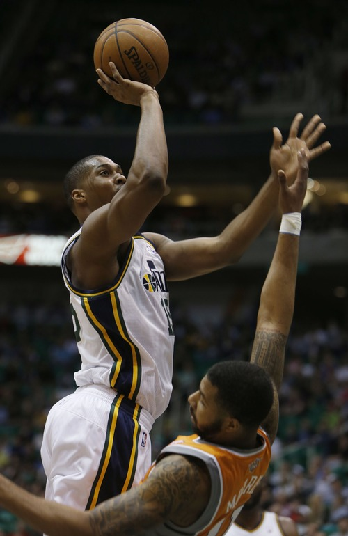 Steve Griffin | The Salt Lake Tribune   Utah's Derrick Favors crashes into Suns forward Markief Morris and is called for a charge during first half action in the Jazz versus Suns NBA game at EnergySolutions Arena in Salt Lake City, Utah Wednesday March 27, 2013.