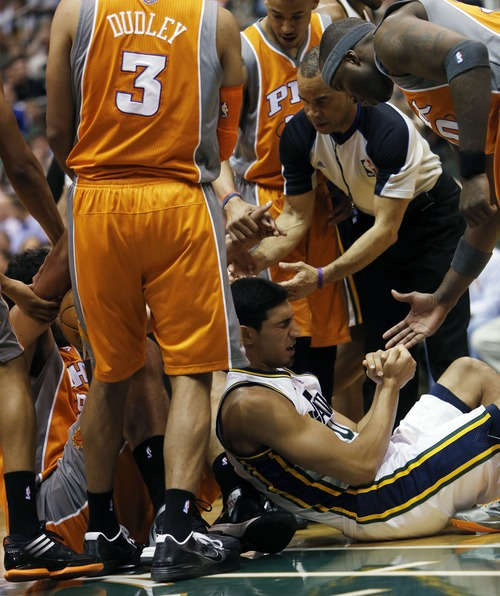 Steve Griffin | The Salt Lake Tribune   Utah's Enes Kanter holds his arms as he sits at the bottom of a pile during first half action in the Jazz versus Suns NBA game at EnergySolutions Arena in Salt Lake City, Utah Wednesday March 27, 2013. Kanter dislocated his shoulder on the play.