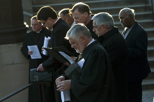 """Chris Detrick     The Salt Lake Tribune The Rev. Michael J. Imperiale, pastor of First Presbyterian Church, and other faith leaders pray during the Good Friday Procession of the Cross Friday March 29, 2013. Since 1983, the Salt Lake Council of Churches has sponsored this annual procession, which is similar to the tradition of the """"Via Dolorosa"""" (Way of Suffering), where pilgrims to Jerusalem follow the path Jesus took to the cross."""