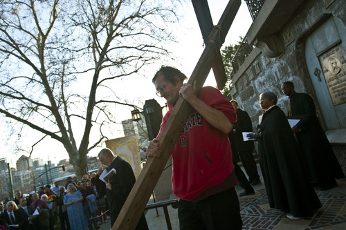 """Chris Detrick     The Salt Lake Tribune Alex Bury, of Sunset, carries a wooden cross from the Cathedral of the Madeleine to First Presbyterian Church during the Good Friday Procession of the Cross Friday March 29, 2013. Since 1983, the Salt Lake Council of Churches has sponsored this annual procession, which is similar to the tradition of the """"Via Dolorosa"""" (Way of Suffering), where pilgrims to Jerusalem follow the path Jesus took to the cross."""