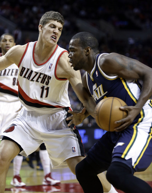 Utah Jazz forward Paul Milsap, right, drives to the basket against Portland Trail Blazers center Meyers Leonard during the first quarter of an NBA basketball game in Portland, Ore., Friday, March 29, 2013.(AP Photo/Don Ryan)