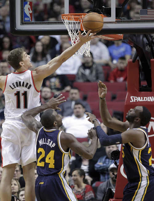 Portland Trail Blazer center Meyers Leonard, left, shoots over Utah Jazz center Al Jefferson, right, and forward Paul Milsap during the first quarter of an NBA basketball game in Portland, Ore., Friday, March 29, 2013.(AP Photo/Don Ryan)