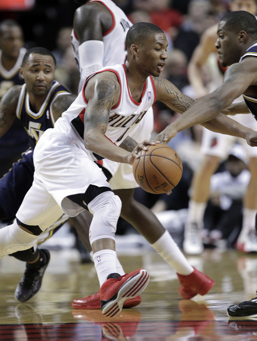 Portland Trail Blazers guard Damian Lillard, middle, drives past Utah Jazz guard Mo Wiliams, left, and against Jazz forward Derrick Favors during the first quarter of an NBA basketball game in Portland, Ore., Friday, March 29, 2013.(AP Photo/Don Ryan)