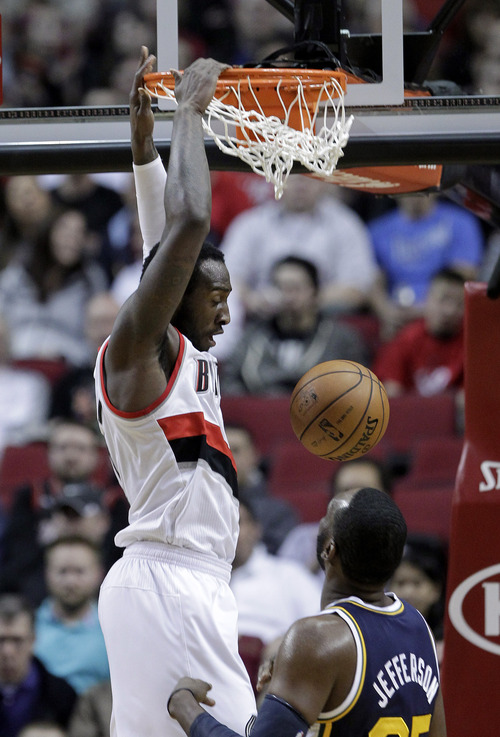 Portland Trail Blazers center J.J. Hickson, left, scores over Utah Jazz center Al Jefferson during the first quarter of an NBA basketball game in Portland, Ore., Friday, March 29, 2013.(AP Photo/Don Ryan)