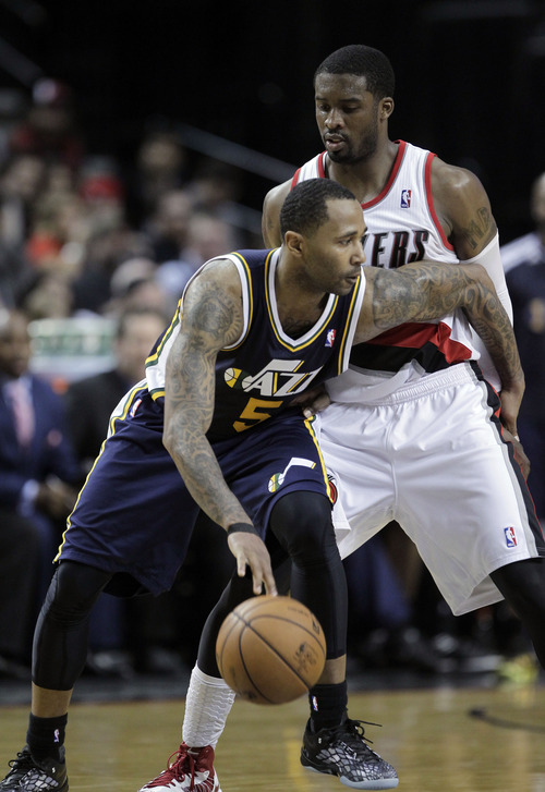 Utah Jazz guard Mo Williams, left, works to dribble around Portland Trail Blazers guard Wesley Matthews during the second half of an NBA basketball game in Portland, Ore., Friday, March 29, 2013.  Williams led the Jazz in scoring with 28 points as they beat the Trail Blazers 105-95. (AP Photo/Don Ryan)