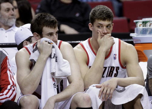 The Portland Trail Blazers' Victor Claver, left, from Spain, and Meyers Leonard sit on the bench during the final moments of an NBA basketball game against the Utah Jazz in Portland, Ore., Friday, March 29, 2013.  Utah won 105-95. (AP Photo/Don Ryan)
