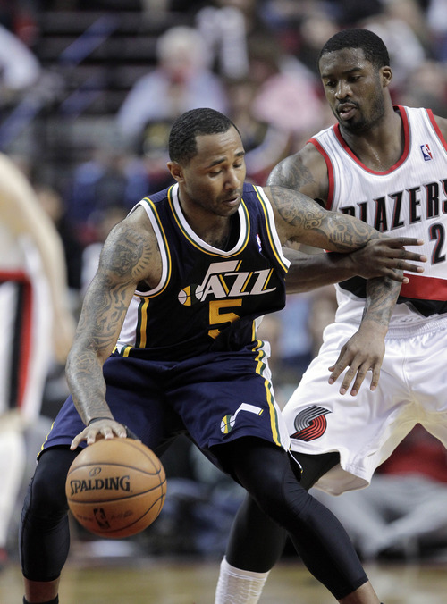 Utah Jazz guard Mo Williams, left, holds off Portland Trail Blazers guard Wesley Matthews while dribbling during the second half of an NBA basketball game in Portland, Ore., Friday, March 29, 2013.  Williams led the Jazz in scoring with 28 points as they beat the Trail Blazers 105-95. (AP Photo/Don Ryan)