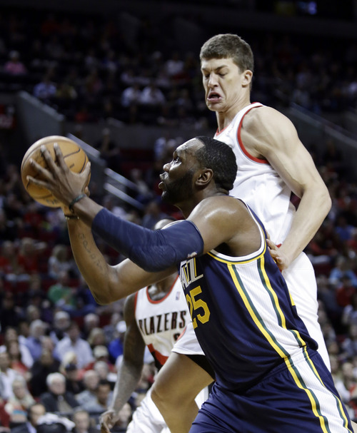 Utah Jazz center Al Jefferson, left, drives to the basket past Portland Trail Blazers center Meyers Leonard during the first quarter of an NBA basketball game in Portland, Ore., Friday, March 29, 2013.(AP Photo/Don Ryan)