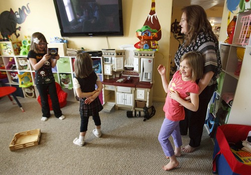 Leah Hogsten  |  The Salt Lake Tribune Suzanne Larson tickles Piper, 7, as her sisters Allie, 9, and Jeni, 6, take pictures of themselves. Suzanne and Richard Larson live in Layton with 10 of their 19 children, Friday, March 22, 2013.