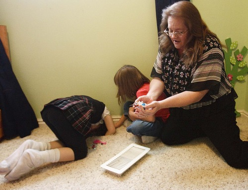 Leah Hogsten  |  The Salt Lake Tribune Suzanne Larson helps her daughters Jeni, 6, and Piper, 7, pull toys and other objects out of the vents in Jeni's room. Suzanne and Richard Larson live in Layton with 10 of their 19 children, Friday, March 22, 2013.