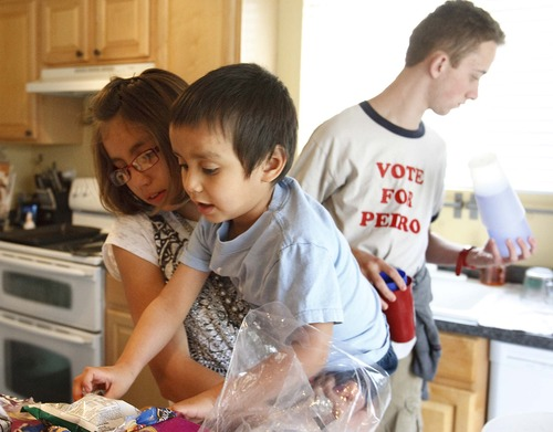 Leah Hogsten  |  The Salt Lake Tribune Kenlee, 11, helps her brother Justus, 4, pick out chips for dinner while Preston, 18, fills glasses for his siblings. Suzanne and Richard Larson live in Layton with 10 of their 19 children, Friday, March 22, 2013.