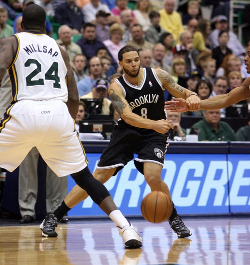 Kim Raff  |  The Salt Lake Tribune (middle) Brooklyn Nets point guard Deron Williams (8) passes the ball past (left) Utah Jazz power forward Paul Millsap (24) during the second half at EnergySolutions Arena in Salt Lake City on March 30, 2013.  The Jazz won the game 116-107.