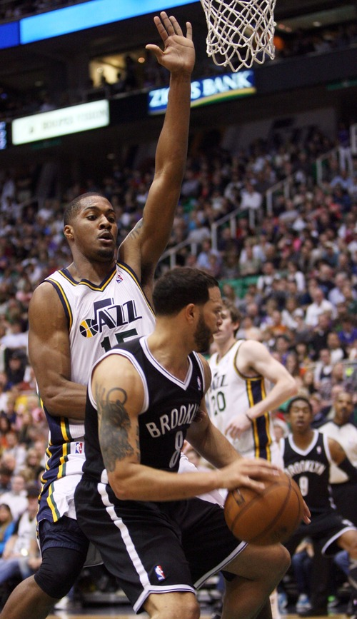 Kim Raff  |  The Salt Lake Tribune (bottom) Brooklyn Nets point guard Deron Williams (8) drives the basket as he is defended by Utah Jazz power forward Derrick Favors (15) during the second half at EnergySolutions Arena in Salt Lake City on March 30, 2013.  The Jazz won the game 116-107.