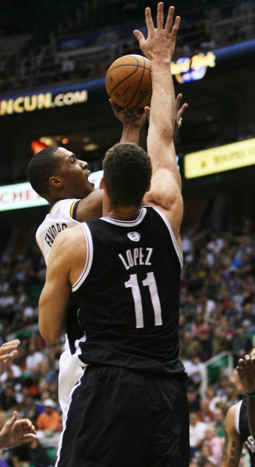 Kim Raff  |  The Salt Lake Tribune (left) Utah Jazz power forward Derrick Favors (15) takes a shot as he is defended by Brooklyn Nets center Brook Lopez (11) during the first half at EnergySolutions Arena in Salt Lake City on March 30, 2013.