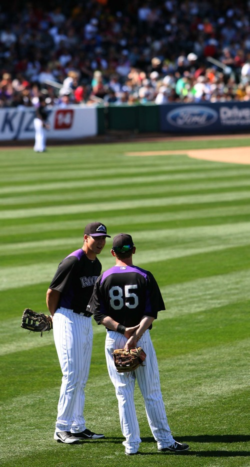 Leah Hogsten  |  The Salt Lake Tribune Colorado Rockies outfielder Matt Mc Bride and David Kandilas chat in the outfield during a pitching change. Seattle defeated Colorado 4-3, Saturday, March 30, 2013, in the final exhibition tuneup of spring training as 15,411 spectators enjoyed the first Major League Baseball game played in Salt Lake City since 1970 at  Spring Mobile Ballpark.