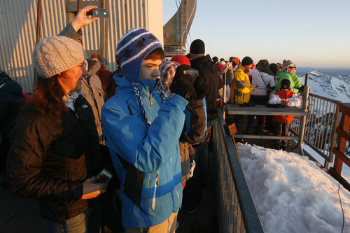 Scott Sommerdorf   |  The Salt Lake Tribune Visitors on Hidden Peak take photos of the rising sun. Snowbird hosted an Easter sunrise service at 11,000 feet of elevation on Hidden Peak, Sunday, March 31, 2013.