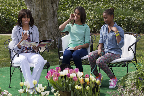 """First lady Michelle Obama, with daughters Malia and Sasha, reads the book """"Cloudy With A Chance of Meatballs"""" to children as part of the annual White House Easter Egg Roll, Monday, April 1, 2013, on the South Lawn of the White House in Washington. (AP Photo/Jacquelyn Martin)"""