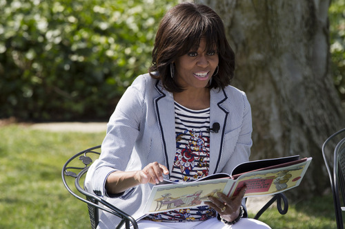 """First lady Michelle Obama reads the book """"Cloudy With A Chance of Meatballs"""" to children as part of the annual White House Easter Egg Roll, Monday, April 1, 2013 on the South Lawn of the White House in Washington. (AP Photo/Jacquelyn Martin)"""
