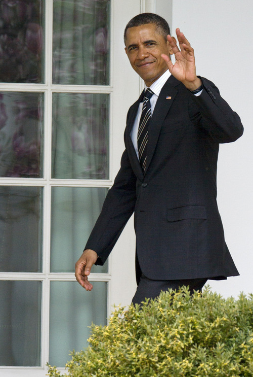 President Barack Obama waves as he enters the Oval Office of the White House in Washington, Monday, April 1, 2013,  after attending the White House Easter Egg Roll on the South Lawn. (AP Photo/Jacquelyn Martin)