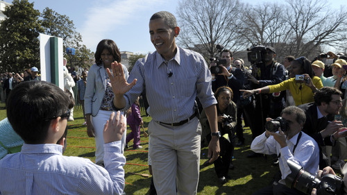 President Barack Obama, accompanied by first lady Michelle Obama, high-fives a participant in the annual Easter Egg Roll on the South Lawn of the White House in Washington, Monday, April 1, 2013. (AP Photo/Susan Walsh)