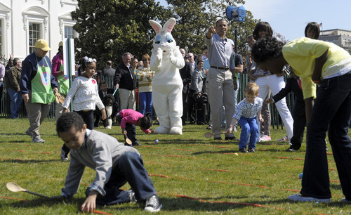 President Barack Obama, standing next to the Easter Bunny, accompanied by first lady Michelle Obama, points to five-year-old Donovan Frazier as he participated in the annual Easter Egg Roll on the South Lawn of the White House in Washington, Monday, April 1, 2013. (AP Photo/Susan Walsh)