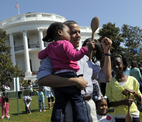 President Barack Obama hold a child after participated in the annual Easter Egg Roll on the South Lawn of the White House in Washington, Monday, April 1, 2013. (AP Photo/Susan Walsh)
