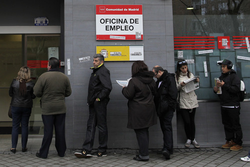 People wait outside an unemployment office in Madrid, Spain, Tuesday, April 2, 2013. Spanish government figures show that the number of people registered as unemployed edged down by a little under 5,000 in March, the first reduction for the month in five years. The scale of the task remains huge though as the number registered as unemployed stands at 5.04 million. Spain is battling to emerge from its second recession in just over three years. (AP Photo/Andres Kudacki)