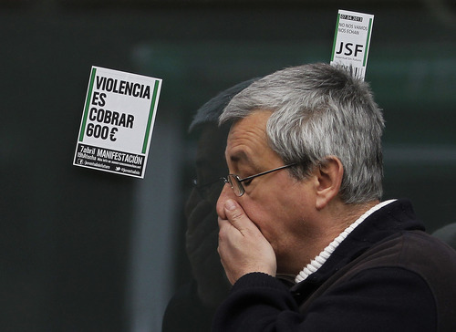 """Stickers reading """"Violence is charged euro 600 a month"""" and """"We are not leaving, they send us away"""" are seen, as a man waits outside an unemployment office in Madrid, Spain, Tuesday, April 2, 2013. Spanish government figures show that the number of people registered as unemployed edged down by a little under 5,000 in March, the first reduction for the month in five years. The scale of the task remains huge though as the number registered as unemployed stands at 5.04 million. Spain is battling to emerge from its second recession in just over three years. (AP Photo/Andres Kudacki)"""