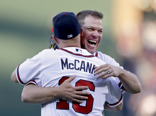 Former Atlanta Braves third baseman Chipper Jones, left, embraces Braves catcher Brian McCann after throwing out the first pitch for an opening day baseball game between the Braves and the Philadelphia Phillies, Monday, April 1, 2013, in Atlanta. (AP Photo/David Goldman)