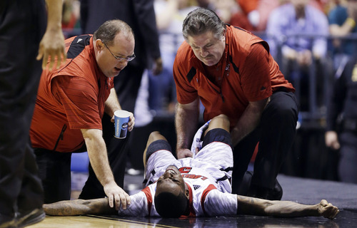 Trainers check on Louisville guard Kevin Ware (5) after Ware injured his lower right leg during the first half of the Midwest Regional final against Duke in the NCAA college basketball tournament, Sunday, March 31, 2013, in Indianapolis. Ware left the court on a stretcher. (AP Photo/Michael Conroy)