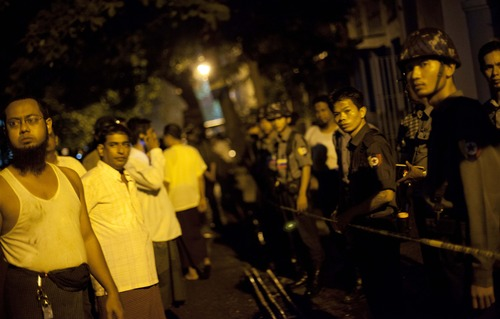 Police officers stand guard outside a mosque that a fire killed 13 children in Yangon, Myanmar, Tuesday, April 2, 2013. Police in Myanmar said 13 children died when an electrical fire broke out at the mosque in the country's largest city. (AP Photo/Gemunu Amarasinghe)