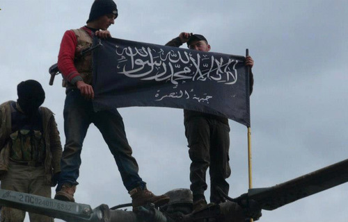 "FILE - In this Friday, Jan. 11, 2013 file citizen journalism image provided by Edlib News Network, ENN, which has been authenticated based on its contents and other AP reporting, shows rebels from al-Qaida affiliated Jabhat al-Nusra waving their brigade flag as they step on the top of a Syrian air force helicopter, at Taftanaz air base that was captured by the rebels, in Idlib province, northern Syria. The Arabic words on the flag reads: ""There is no God only God and Mohamad his prophet, Jabhat al-Nusra."" Last month, militants inside Iraq killed 48 Syrian government troops who had sought refuge from the war in their country _ an ambush that regional officials now say is evidence of a growing cross-border alliance between two powerful Sunni jihadi groups _ Al-Qaida in Iraq and the Nusra Front in Syria.   The U.S. designates both as terrorist organizations, and the purported alliance is further complicating the equation for the West as it weighs how much to support the rebel movement.(AP Photo/Edlib News Network ENN, File)"