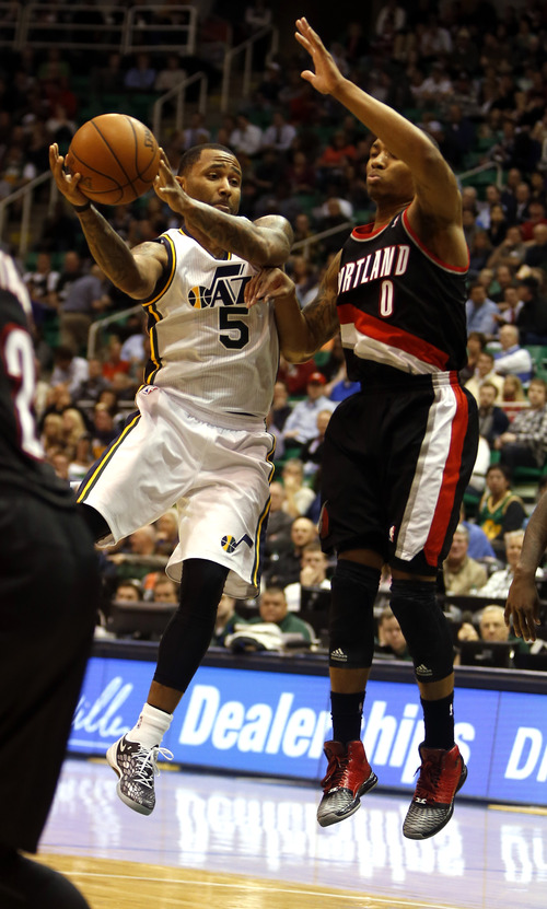 Rick Egan  | The Salt Lake Tribune   Trail Blazers point guard Damian Lillard (0) defends as Utah Jazz point guard Mo Williams (5) takes the ball inside, in NBA action, as the Jazz faced the Portland Trailblazers, at EnergySolutions Arena, Monday, April 1, 2013.