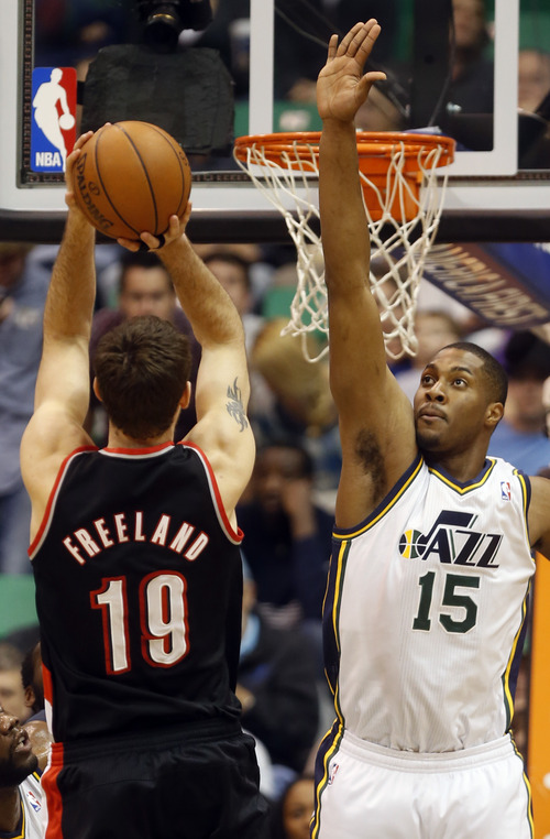 Rick Egan  | The Salt Lake Tribune   Trail Blazers power forward Joel Freeland (19),shoots over Utah Jazz power forward Derrick Favors (15), in NBA action, as the Jazz faced the Portland Trailblazers, at EnergySolutions Arena, Monday, April 1, 2013.