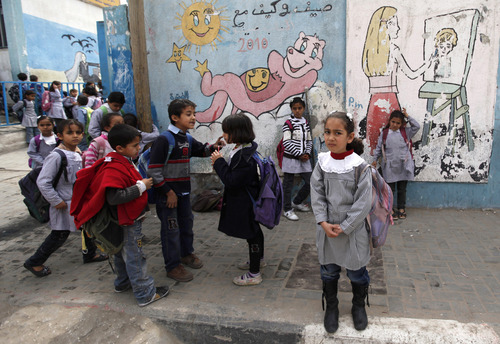 Palestinian school girls and boys walk in front of a the UNRWA elementary school in Shati refugee camp in Gaza City, Tuesday, April 2, 2013. Gaza's Hamas-controlled parliament has passed a law requiring separate classes for boys and girls in public and private schools from the fourth grade. Currently, boys and girls are separated in grade seven in public schools, and private schools can set their own rules. (AP Photo/Hatem Moussa)