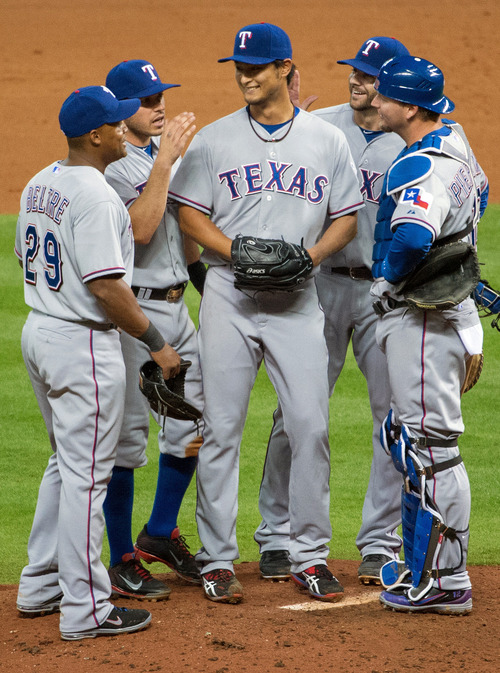 Texas Rangers starting pitcher Yu Darvish is greeted by his teammates as he leaves the game after surrendering a hit in the bottom of the ninth inning against the Houston Astros at Minute Maid Park on Tuesday, April 2, 2013, in Houston. Darvish pitched nine and two-thirds perfect innings before giving up a hit to Astros' Marwin Gonzalez in the Rangers' 7-0 win. (AP Photo/Houston Chronicle, Smiley N. Pool)