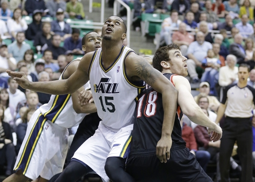 Utah Jazz's Derrick Favors (15) and Portland Trail Blazers' Victor Claver (18) battle under the boards for a rebound in the second half during an NBA basketball game Monday, April 1, 2013, in Salt Lake City.  (AP Photo/Rick Bowmer)