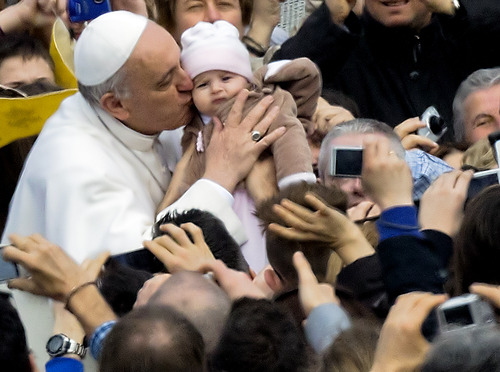 Pope Francis kisses a child as he tours St. Peter's Square at the Vatican in his popemobile prior to his weekly general audience, Wednesday, April 3, 2013. (AP Photo/Domenico Stinellis)