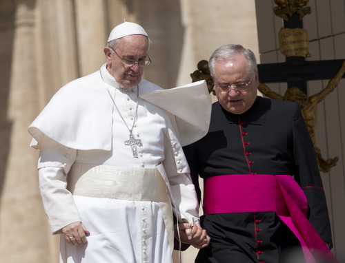 Pope Francis walks down helped by father Leonardo Sapienza after his weekly general audience in St. Peter square at the Vatican Wednesday, April 3, 2013. (AP Photo/Alessandra Tarantino)