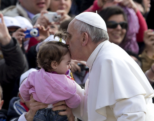 Pope Francis kisses a child during his weekly general audience in St. Peter square at the Vatican Wednesday, April 3, 2013. (AP Photo/Alessandra Tarantino)