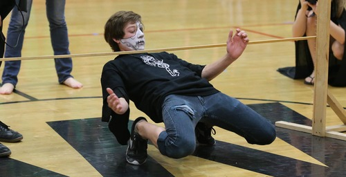 Paul Fraughton  |   Salt Lake Tribune West High School junior Dyki Rose concentrates as he slides beneath the limbo stick. His efforts were enough to win the limbo contest at the school's Spirit Bowl, one of the activities at  Spirit Week.