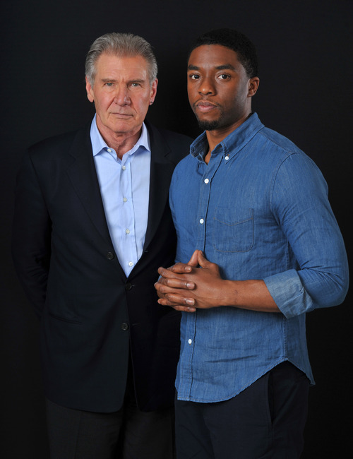"In this Saturday, March 23, 2013 photo, Harrison Ford, left, and Chadwick Boseman, cast members in the film ""42,"" pose together for a portrait, in Los Angeles. In the new movie by writer-director, Brian Helgeland, Boseman plays Jackie Robinson and Ford plays Brooklyn Dodgers president and general manager Branch Rickey.  Boseman, who bears a remarkable resemblance to Robinson, grew up playing basketball but said he learned of Robinson's importance around the same time he first learned of Martin Luther King Jr.'s crucial role in fighting for civil rights.  (Photo by Chris Pizzello/Invision/AP)"
