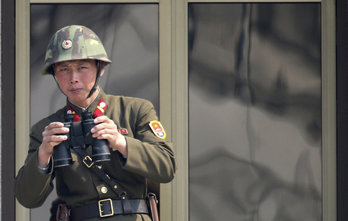 "A North Korean soldier watches the South Korean side at the border village of Panmunjom in the demilitarized zone (DMZ) in South Korea Thursday, April 4, 2013. South Korea's defense minister said Thursday North Korea has moved a missile with ""considerable range"" to its east coast, but said it is not capable of hitting the United States. (AP Photo/Yonhap, Lee Jong-hoon)"