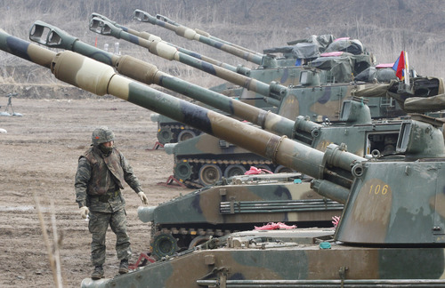 A South Korean Marine stands on a K-55 self-propelled howitzer during a military exercise against possible attacks by North Korea near the border village of Panmunjom in Paju, South Korea, Wednesday, April 3, 2013. (AP Photo/Ahn Young-joon)