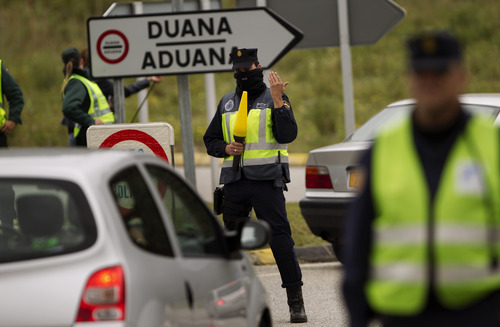 Police officers stand guard as they control the vehicles entering in Spain from France in La Jonquera, Girona, Spain, Saturday, April 28, 2012. Spain has temporarily restored border checks in its northeast and at two major airports in a bid to stop protesters entering the country ahead of a European Central Bank meeting in Barcelona. Spanish authorities early Saturday suspended the Schengen Treaty which allows unrestricted travel inside member nations, and imposed controls at six border crossings with France and at Barcelona and Gerona international airports.  (AP Photo/Emilio Morenatti)