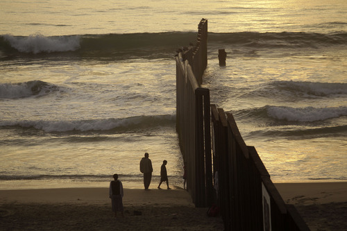 People hang out in the beach next to the border fence separating Mexico from the U.S. as the day comes to an end in Tijuana, Mexico, Saturday, Sept. 22, 2012.  (AP Photo/Dario Lopez-Mills)