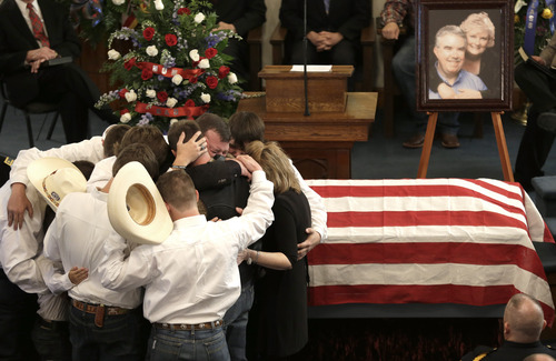The family of Kaufman County District Attorney Mike McLelland and his wife, Cynthia, comfort each other during their funeral services at  the First Baptist Church of Wortham Friday, April 5, 2013, in Wortham, Texas.  The couple was found shot to death Saturday in their house near Forney, about 20 miles east of Dallas. No arrests have been made. (AP Photo/LM Otero)