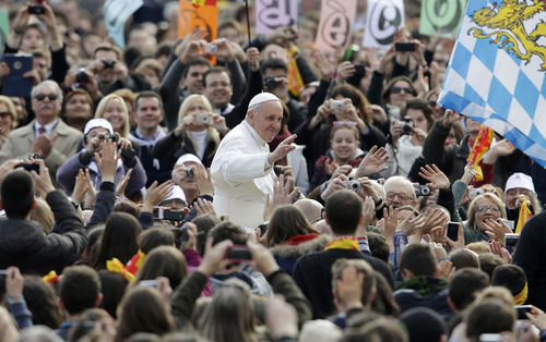 Pope Francis salutes as he arrives for his weekly general audience in St. Peter square at the Vatican Wednesday, April 3, 2013. (AP Photo/Alessandra Tarantino)