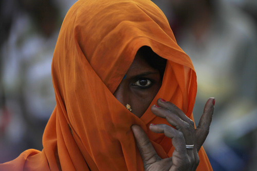 A veiled Indian woman watches as she stands on a field at Phaphamau on the outskirts of Allahabad, India, Friday, April 5, 2013. (AP Photo/Rajesh Kumar Singh)